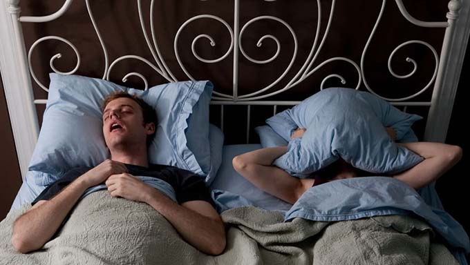 C6564B Young man snoring, woman covering face with pillow